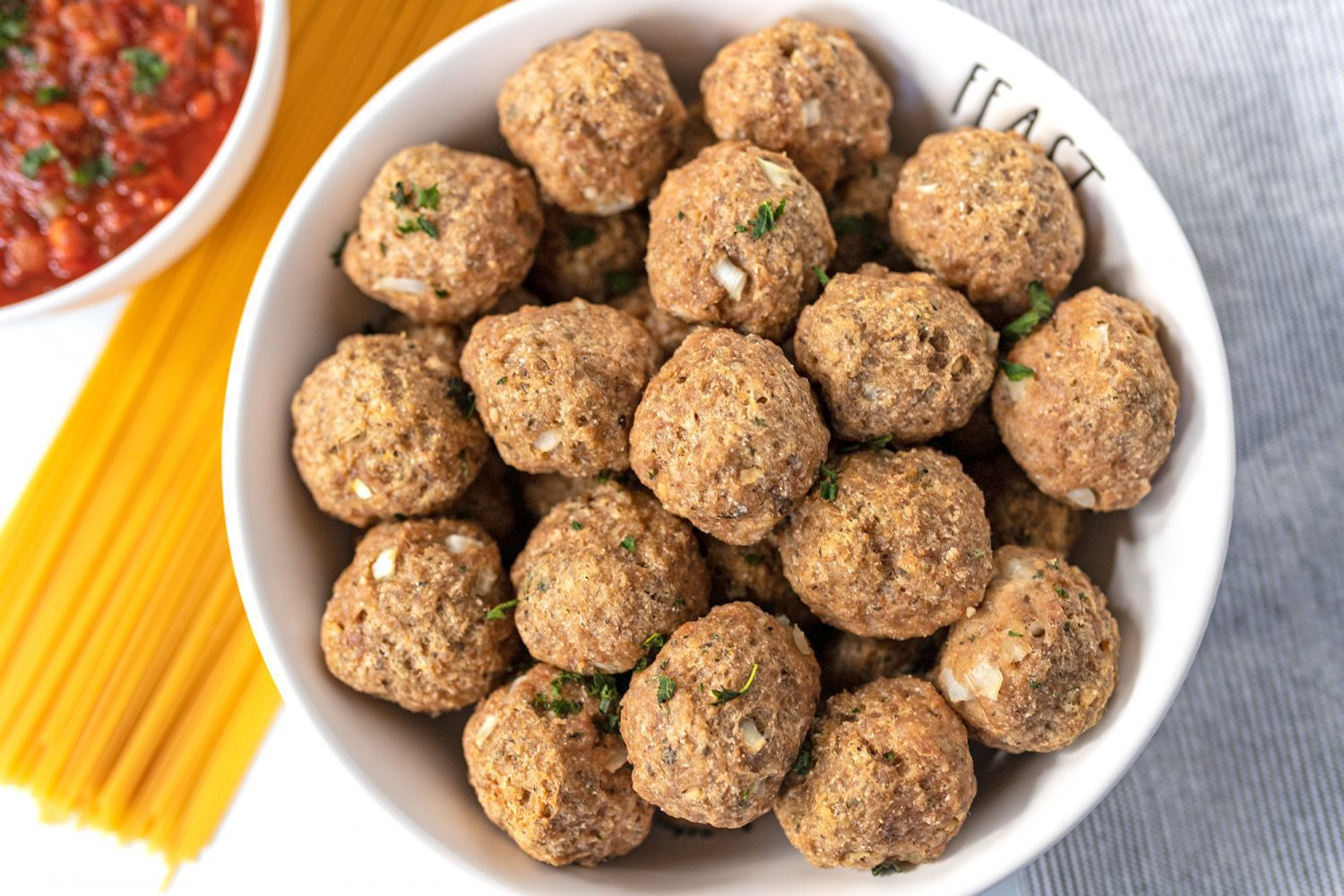 healthier oven-baked meatballs in a bowl next to spaghetti