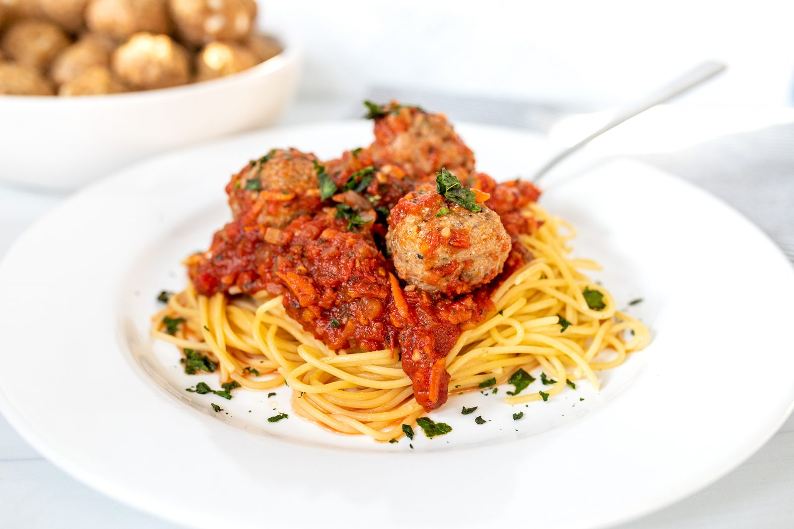 plate of spaghetti with sauce and meatballs