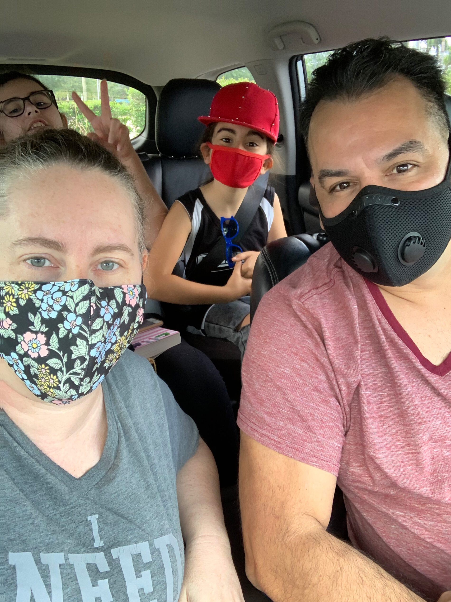 family in the car with masks on getting ready to get vaccinated