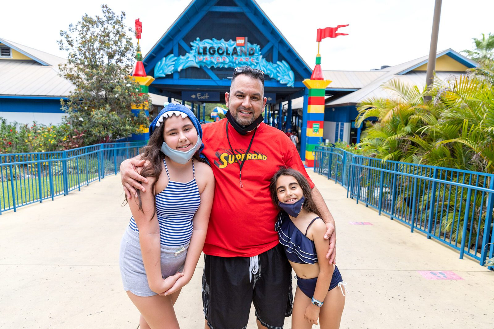 Dad and two girls standing in front of LEGOLAND Water Park sign
