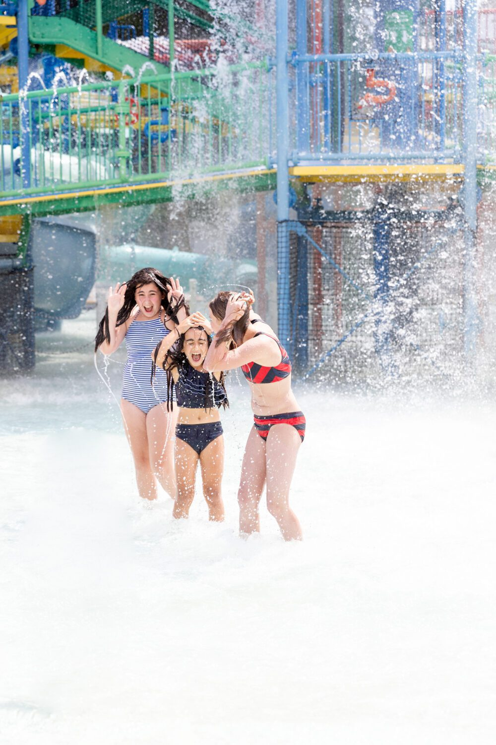 three girls getting water dumped on their heads