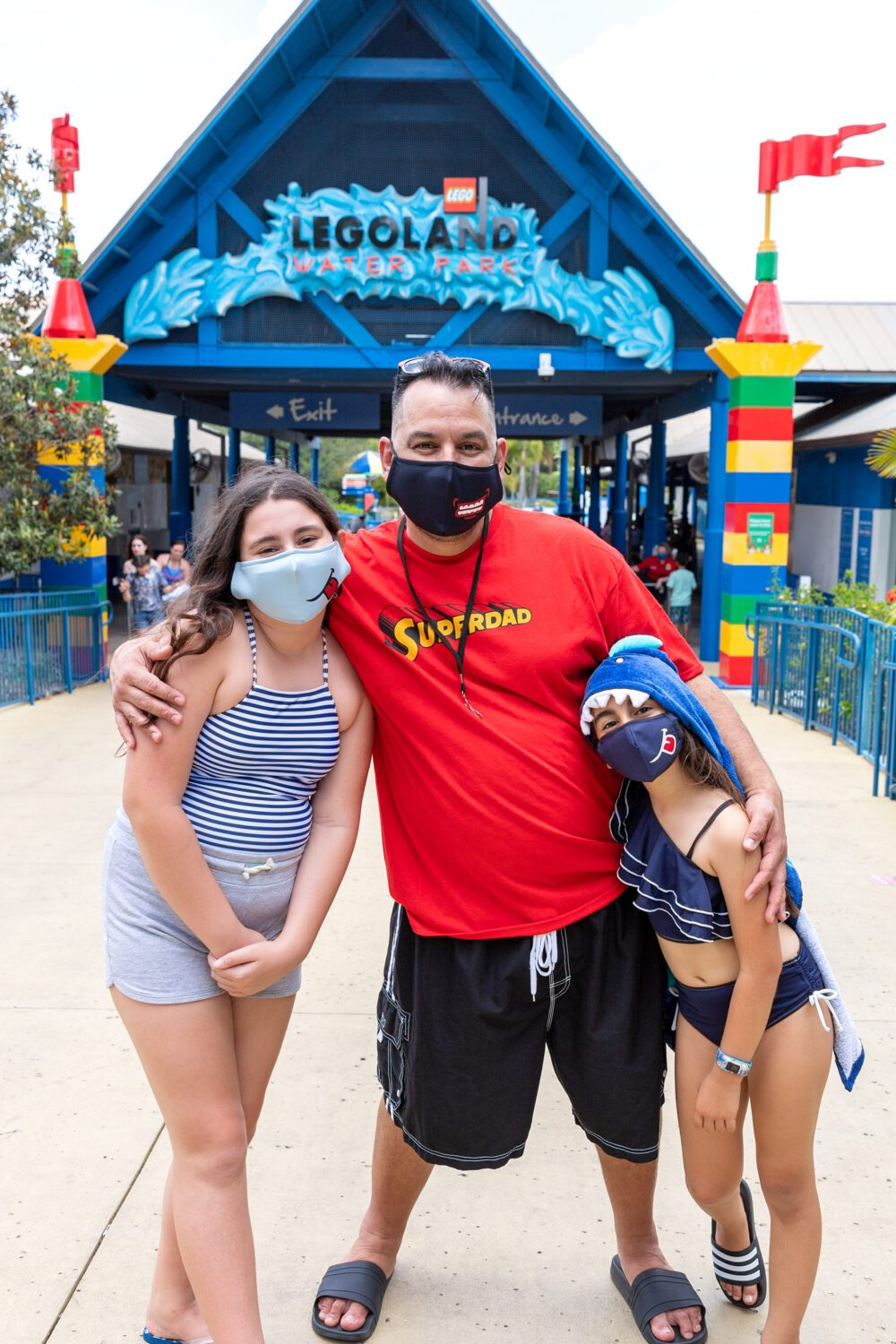 Dad and two girls standing in front of LEGOLAND Water Park sign with masks on
