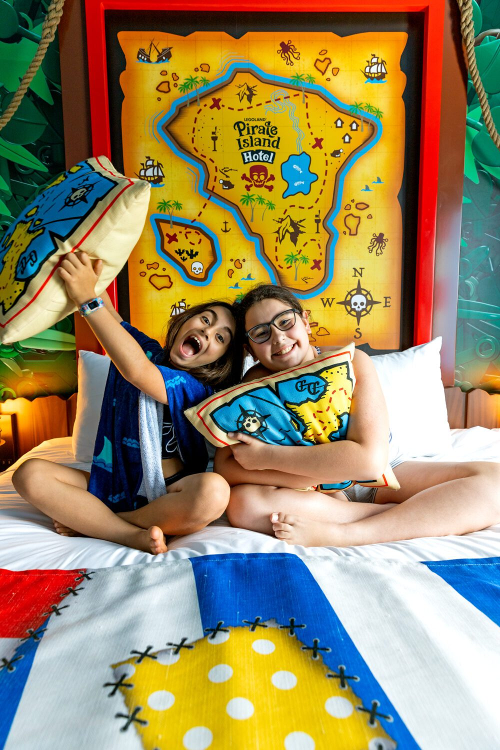two girls sitting on the bed at LEGOLAND Pirate Island Hotel