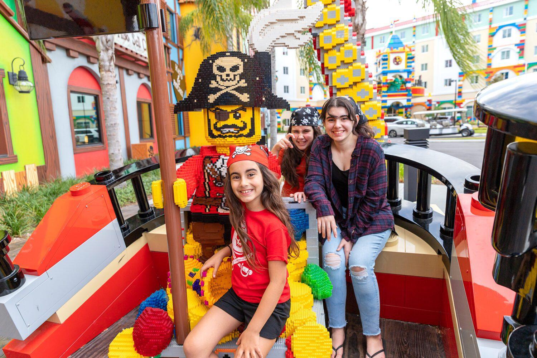 three sisters posing near a pirate ship at LEGOLAND Florida Resort