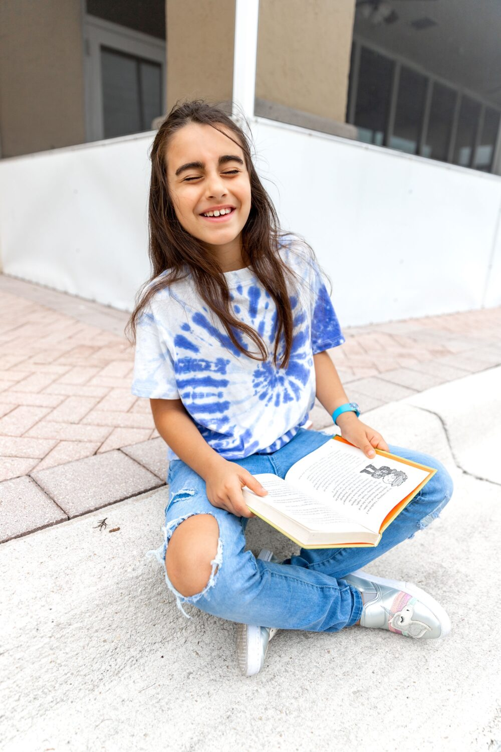 girl laughing with a book in her hand