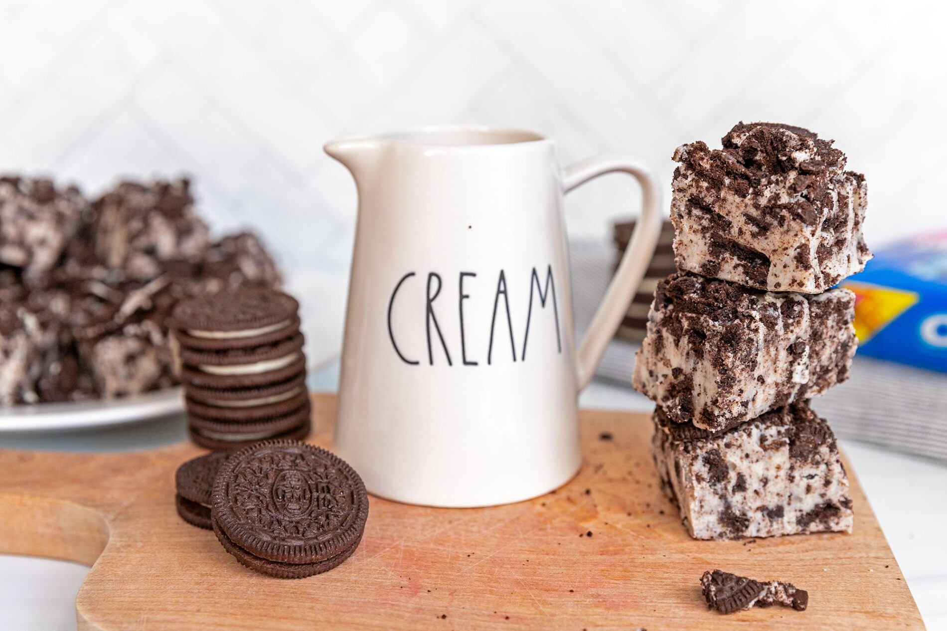 cookies and cream fudge on a cutting board with oreos and a rae dunn cream cup
