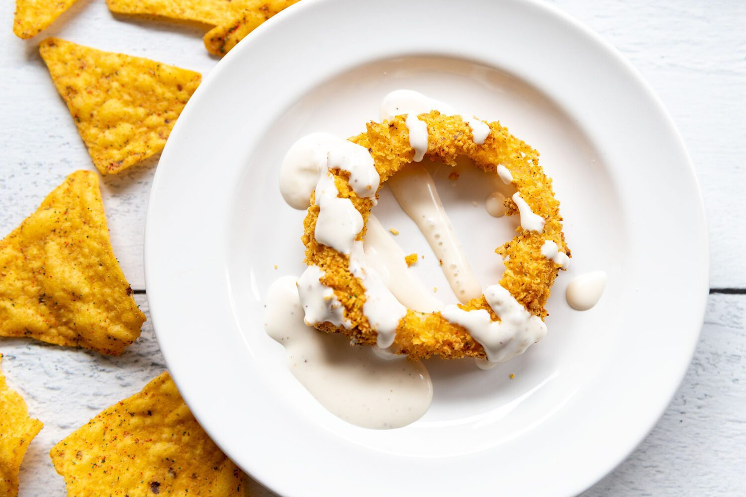 onion ring on a plate covered in ranch dressing