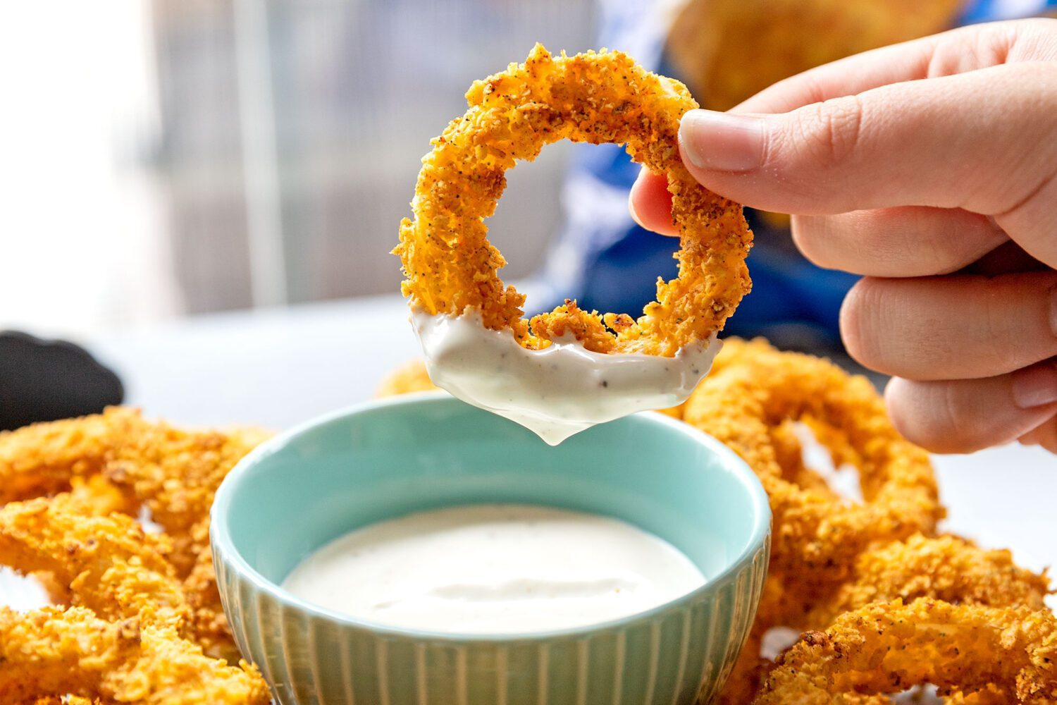 dipping an onion ring into ranch