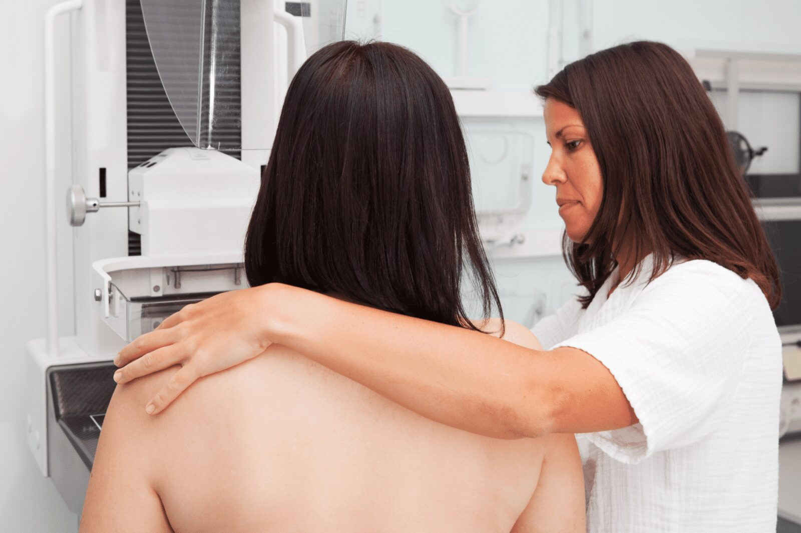 nurse with her arm around a patient getting ready for mammogram