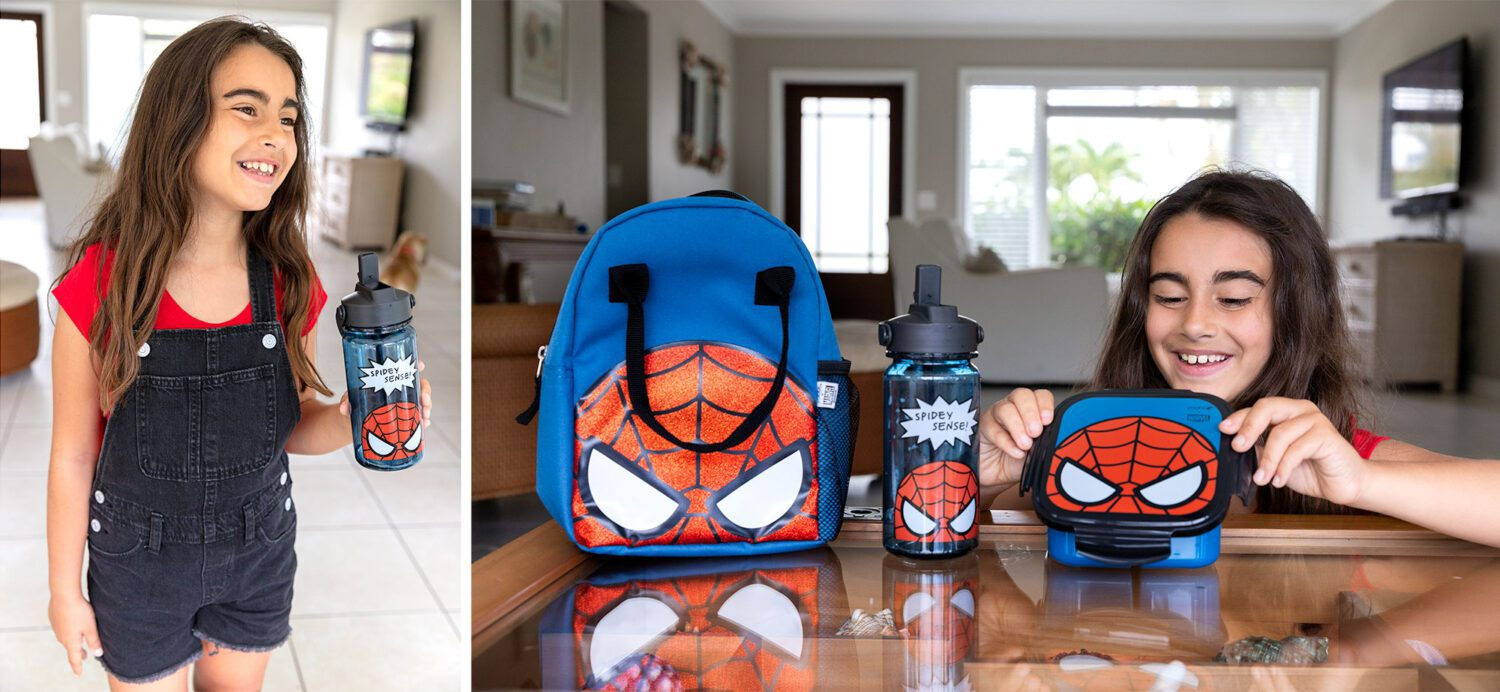 girl sitting at a table with her new spiderman lunchbox, bento box and water bottle