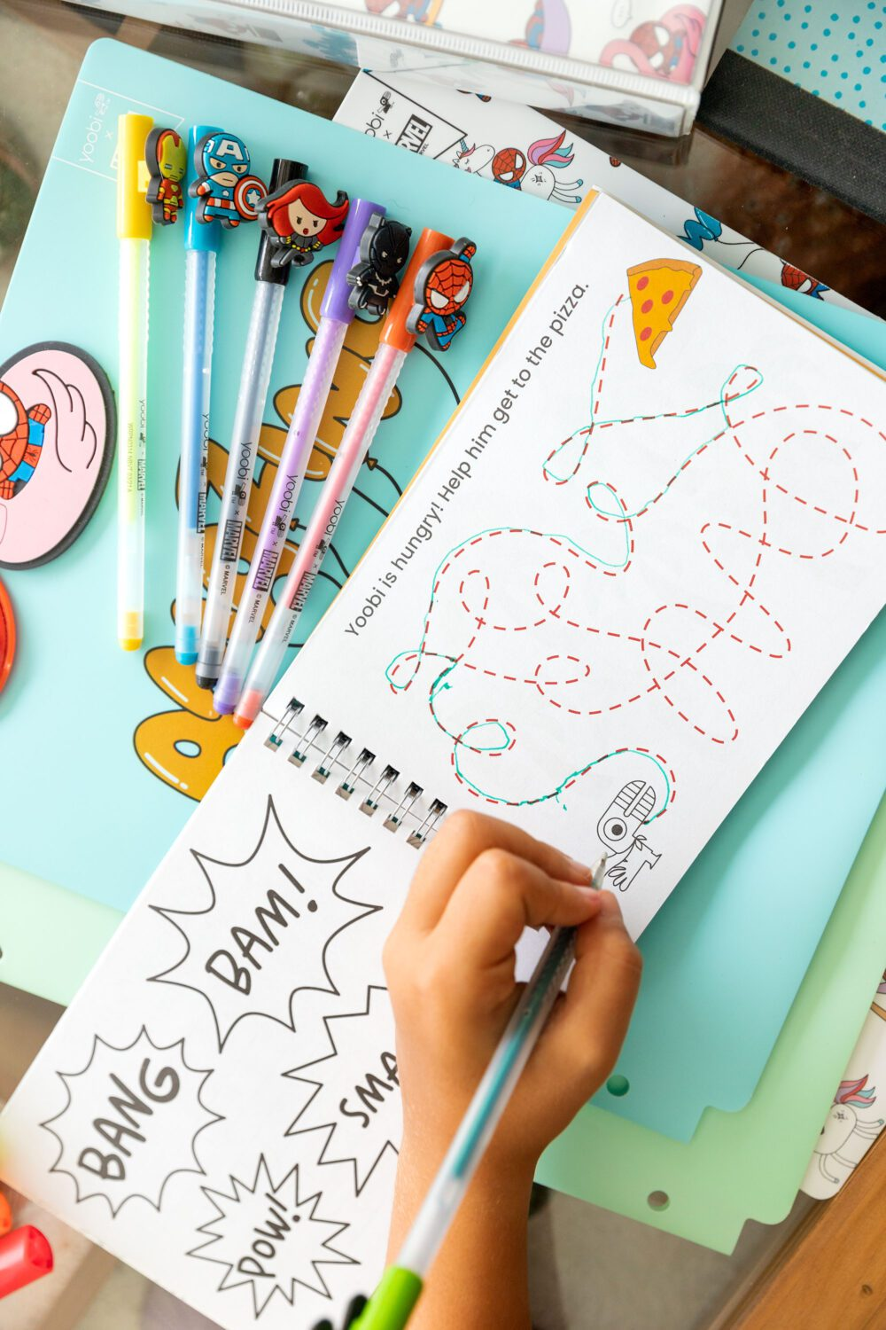 child's hand completing an activity page with superhero pens nearby