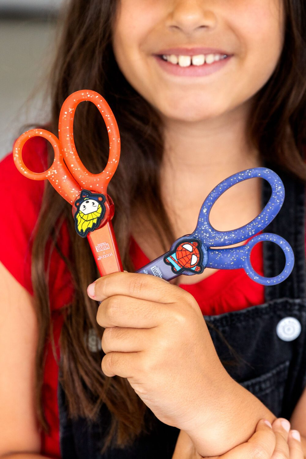 young girl holding two scissors from the yoobi Marvel collection