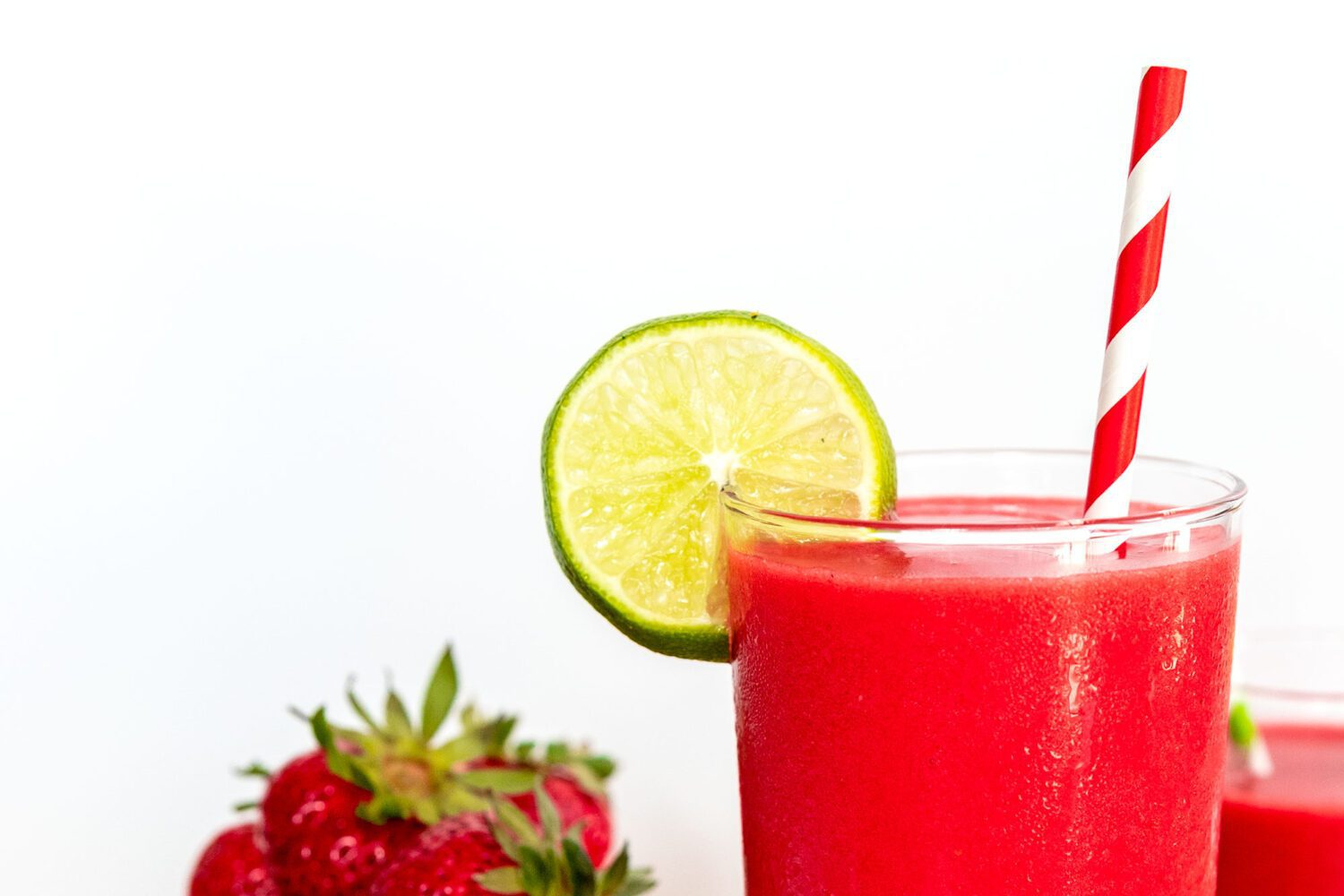 close up of a glass with a red fruity drink