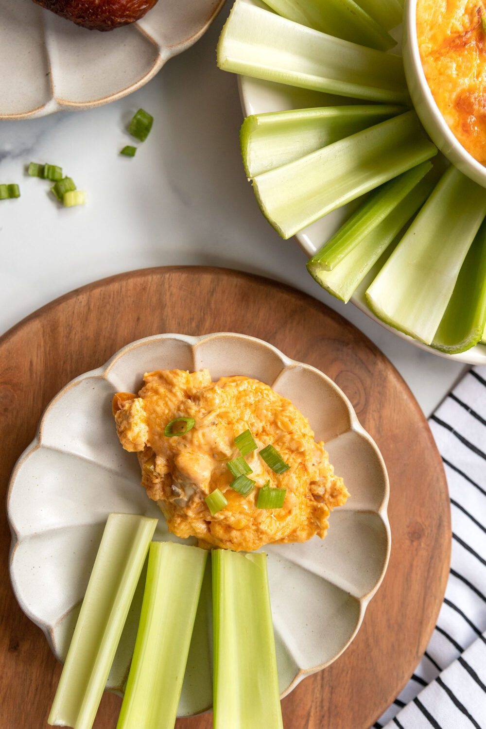 plate with celery sticks and a scoop of buffalo chicken dip