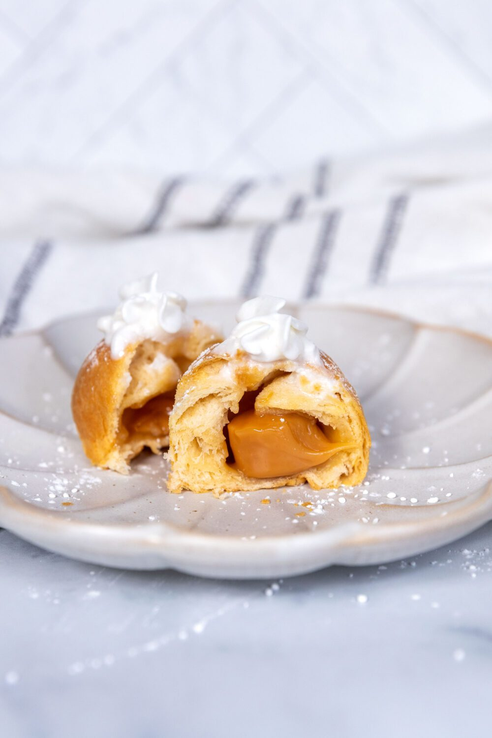 caramel oozing out of a puff with whipped cream on top