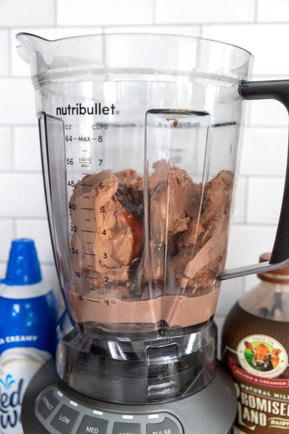 ice cream, chocolate milk and chocolate syrup in a blender