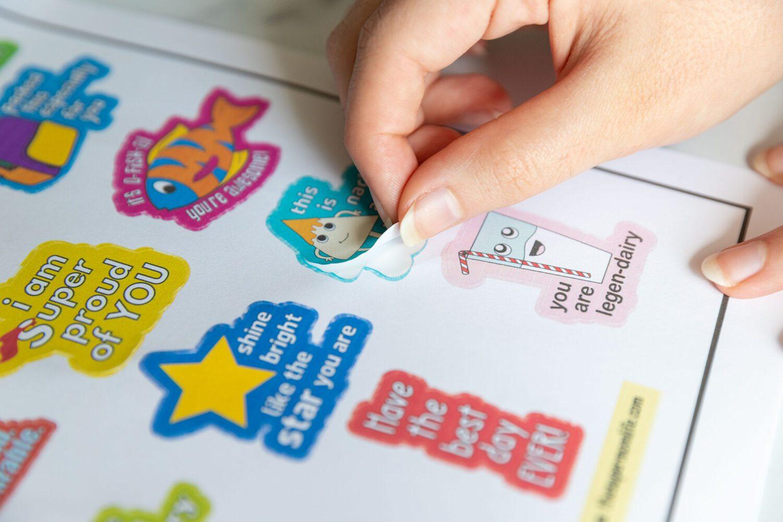 peeling a sticker off of a sheet