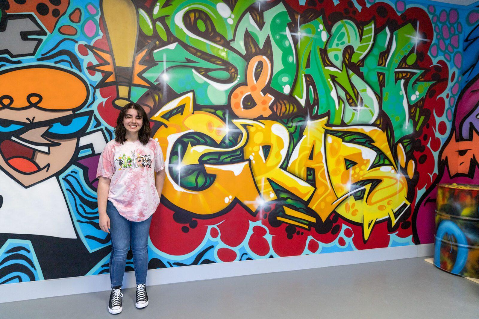teenage girl standing near smash and grab mural