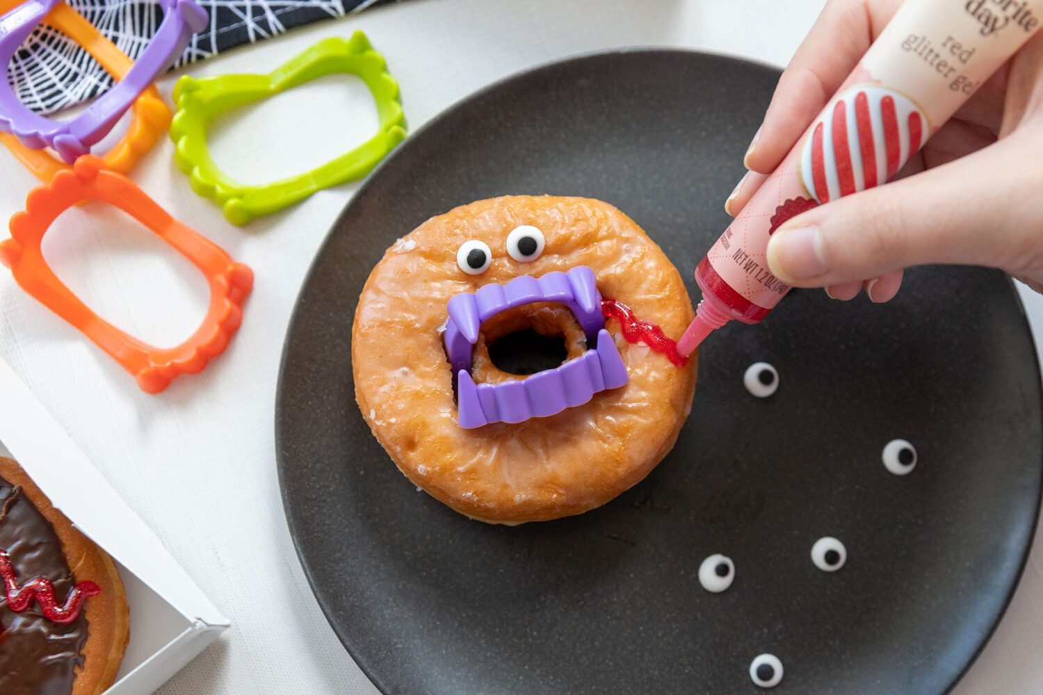 placing red gel on a donut to look like blood