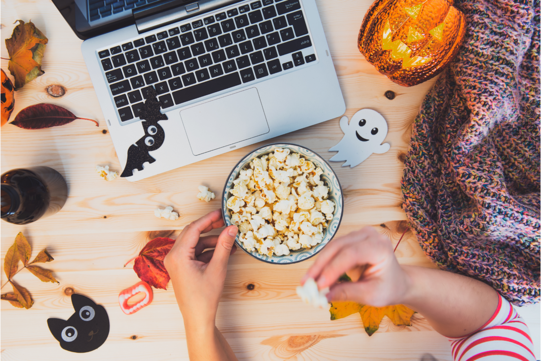 hands grabbing popcorn with Halloween decorations